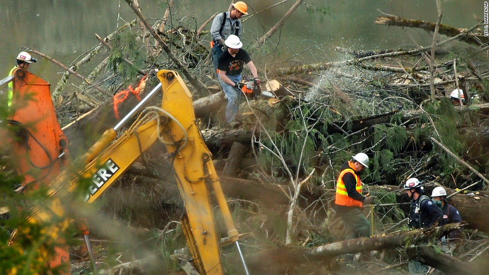 Workers cut a tree next to a possible victim on Sunday, March 30.