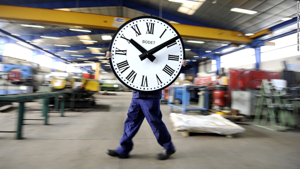 An employee of the Bodet company carries a clock Wednesday, March 26, at a plant in Trementines, France.
