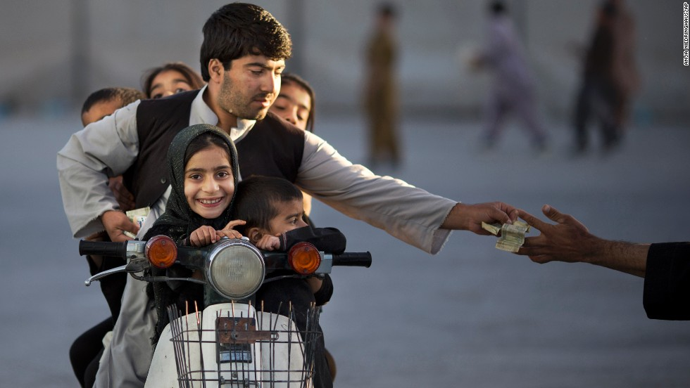 A man with his five children pays money to enter a park in Kandahar, Afghanistan, in November.