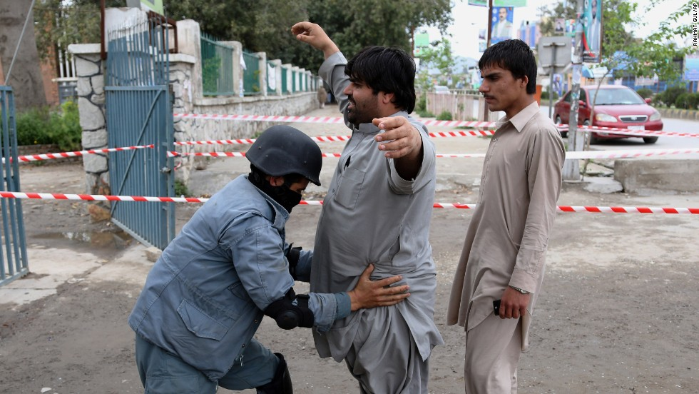 A police officer checks a man at a polling station in Jalalabad.