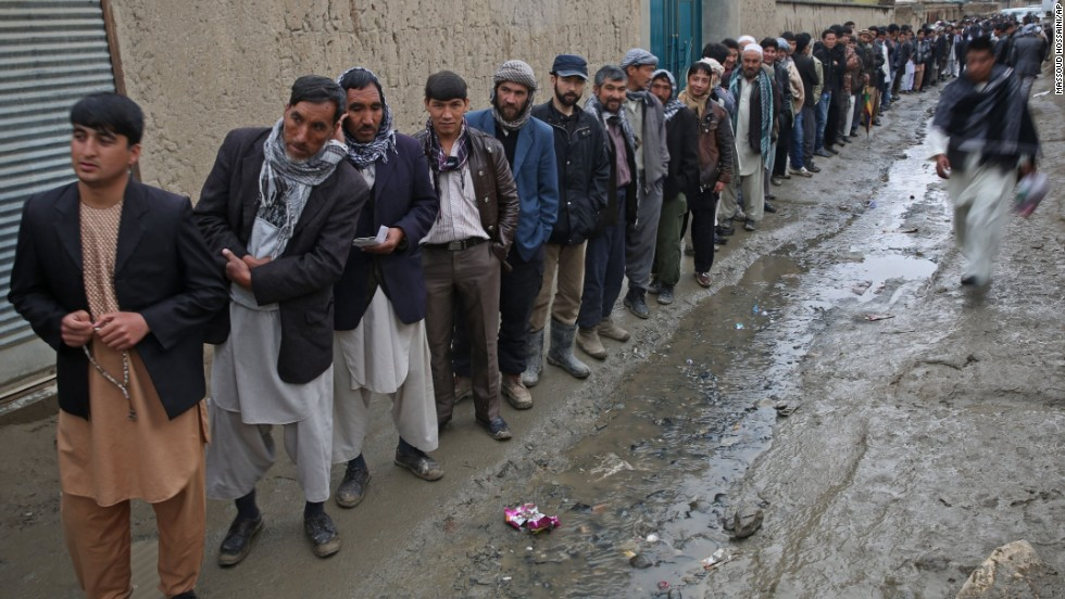 Men line up for registration before voting at a polling station in Kabul.