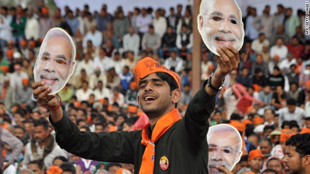 An Indian supporter Narendra Modi holds up masks of the prime ministerial candidate at an election rally.