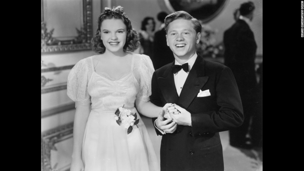 "Rooney hold hands with Garland in a 1940 still from the film ""Andy Hardy Meets Debutante."""