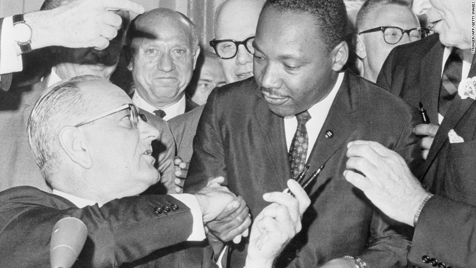 President Lyndon B. Johnson shakes hands with civil rights leader Martin Luther King Jr. after signing the Civil Rights Act of 1964. The LBJ Presidential Library is hosting a Civil Rights Summit this week to mark the 50th anniversary of the legislation.