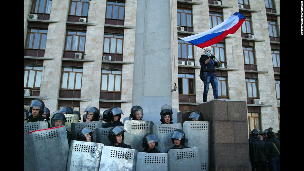 "Protesters wave a Russian flag as they storm the regional administration building in Donetsk on Sunday, April 6. Protesters seized state buildings in several east Ukrainian cities, prompting accusations from Kiev that Moscow is trying to ""dismember"" the country."