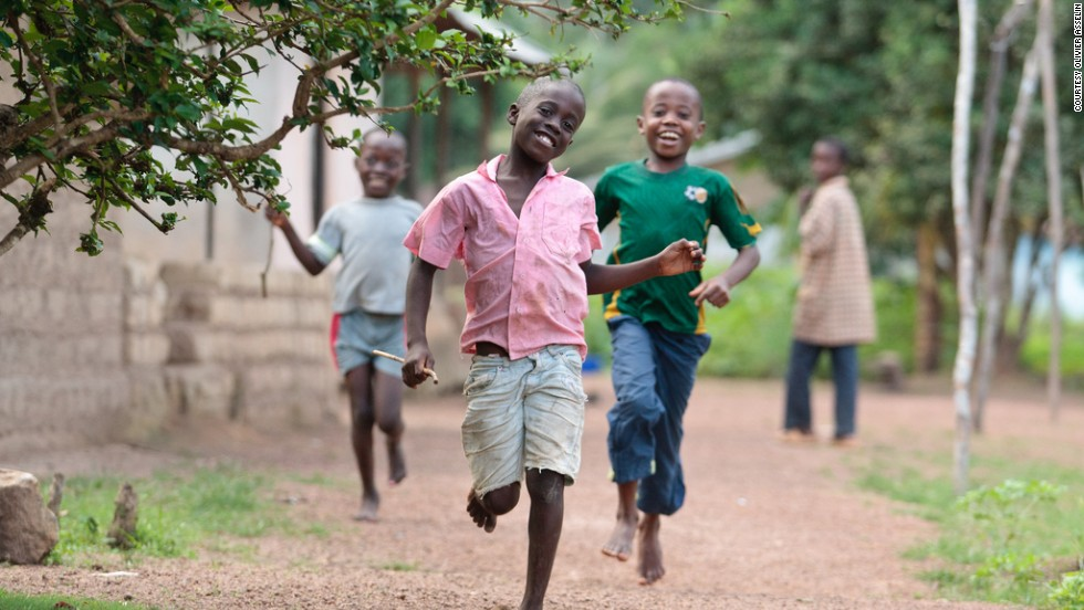 Boys run through the village of Pelewahun, Sierra Leone. Without shoes, they're at high risk for infection with soil-transmitted helminths like hookworm.