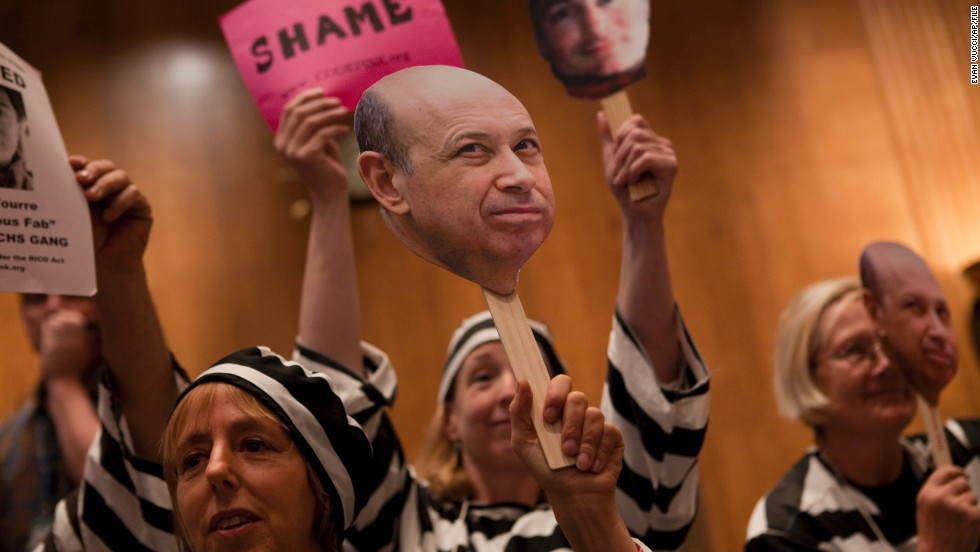 "Today, the top 1% controls about 40% of national wealth. At a hearing in Washington D.C. about Wall Street and the financial crisis, protesters hold a placard depicting Goldman Sachs CEO Lloyd Blankfein, who once famously said, ""I'm doing God's work.""<br />"