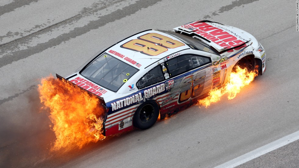 Flames come from the car of Dale Earnhardt Jr. after he crashed early in the NASCAR Sprint Cup race that was held Monday, April 7, at Texas Motor Speedway in Fort Worth, Texas. Earnhardt was OK and able to climb out of his car.
