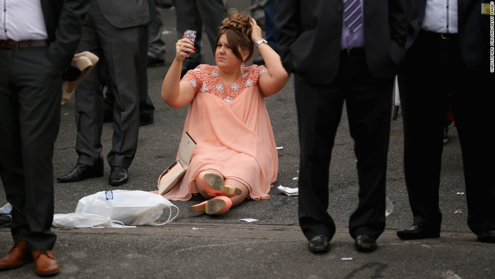 A spectator uses the camera on her cell phone to check her hair on the opening day of the Grand National horse races Thursday, April 3, at Aintree Racecourse in Liverpool, England.