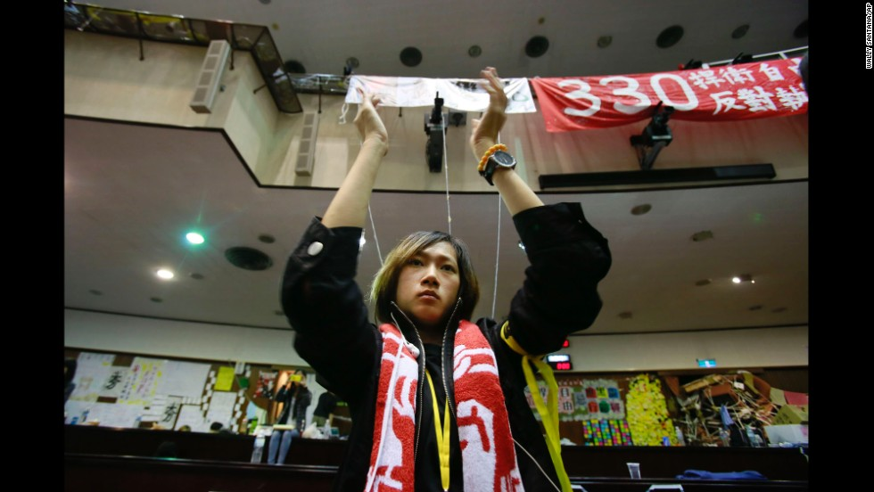 A student protesting a trade pact between Taiwan and China applauds as leaders of the protest speak on the floor of Taiwan's Legislature on Monday, April 7, in Taipei. Protesters, mostly college students, have been camped out in Taiwan's Legislature building since March 18. They say the trade deal with China could harm Taiwan's economy, democratic system and national security. But supporters of the deal have also come out to express themselves.