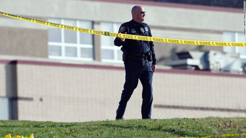 A police officer stands by the scene outside the high school on April 9.