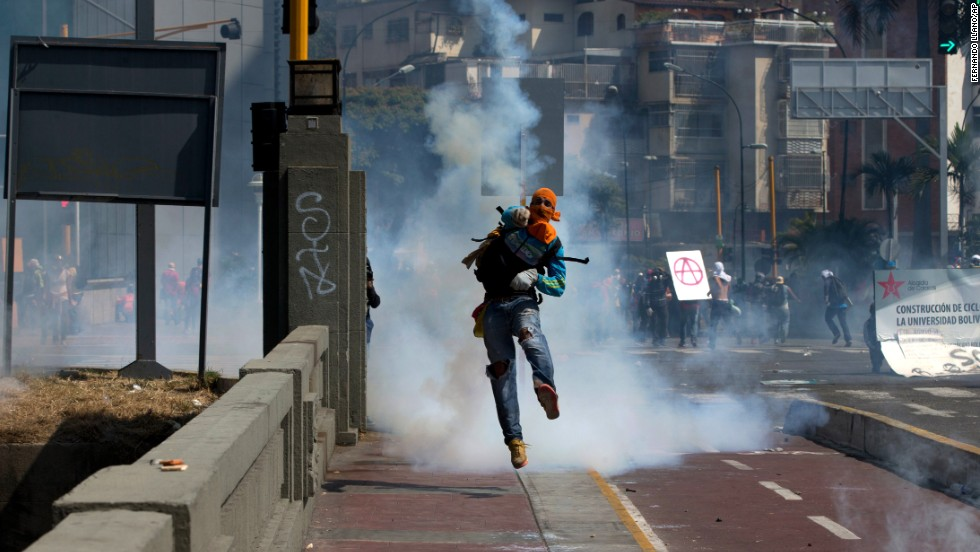 A masked anti-government demonstrator throws a tear gas canister back at National Police during clashes in Caracas on Saturday, April 12.