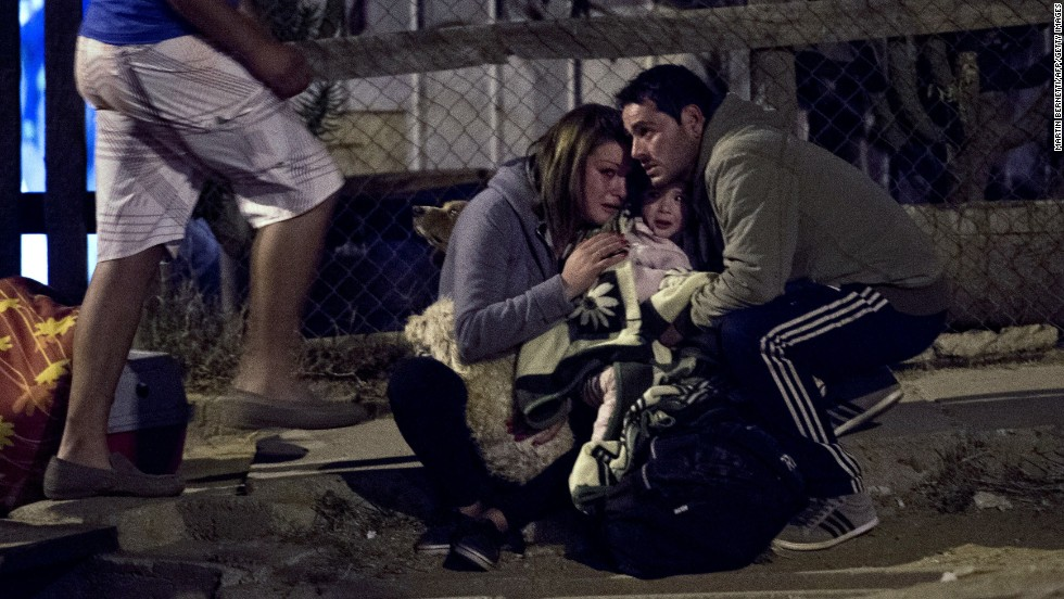 A family huddles in a street in Valparaiso as the city is evacuated April 13.