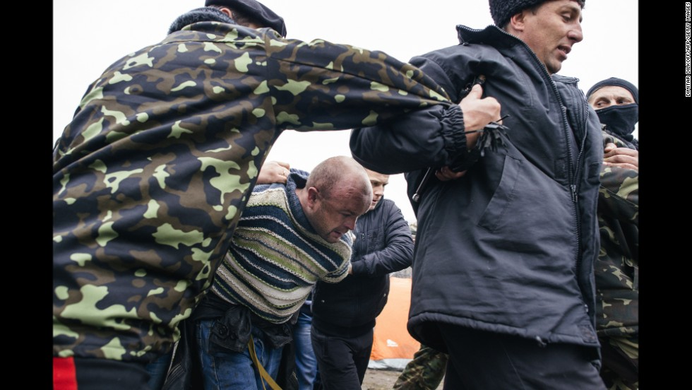 Pro-Russian activists escort a man outside the secret service building in Luhansk on April 13.