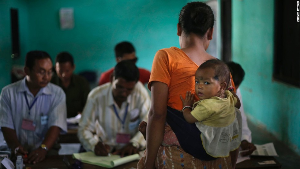 A woman carries her child and waits for her identity to be checked before voting in Diphu, India, on April 12.