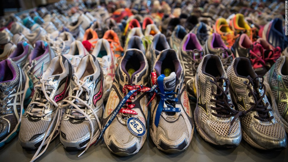 "Running shoes are laid out in a display at the Boston Public Library. It's called ""Dear Boston: Messages from the Marathon Memorial."""