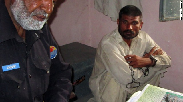 Mohammad Arif Ali (right) sits next to an officer at a police station in Punjab's Bhakkar district on April 14, 2014.
