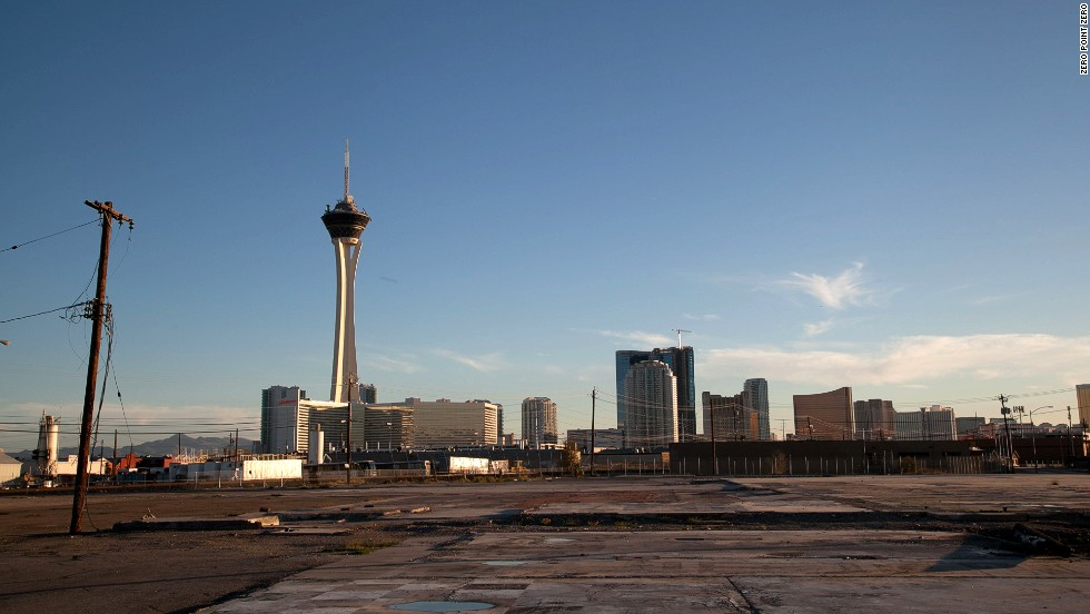 The Vegas skyline and tower of the Stratosphere hotel and casino are seen from an abandoned lot.
