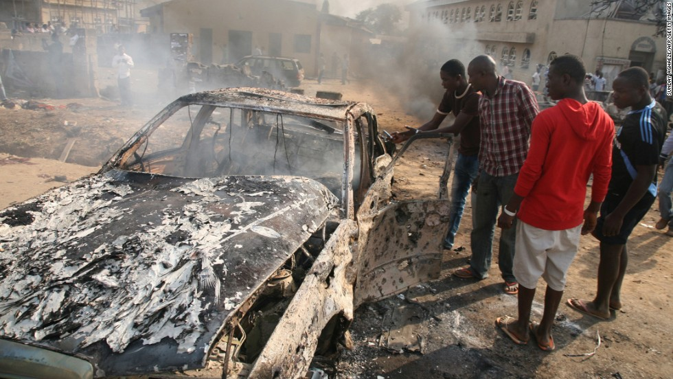 "Men look at the wreckage of a car after a bomb blast at St. Theresa Catholic Church outside Abuja on December 25, 2011. A string of bombs struck churches in five Nigerian cities,<a href=""http://www.cnn.com/2011/12/25/world/africa/nigeria-church-bombing/index.html""> leaving dozens dead and wounded on the Christmas holiday</a>, authorities and witnesses said. Boko Haram's targets included police outposts and churches as well as places associated with ""Western influence."""