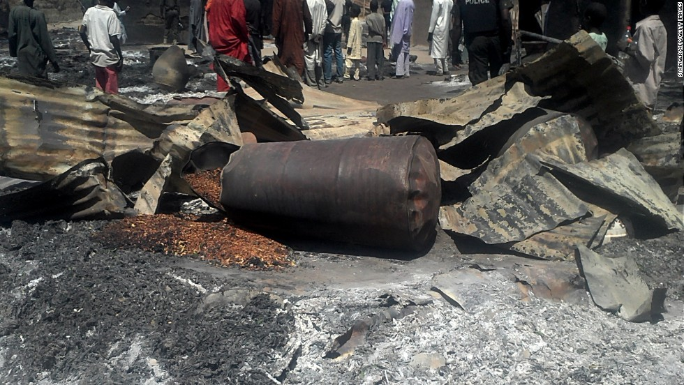 "Police officers stand guard in front of the burned remains of homes and businesses in the village of Konduga on February 12, 2014. Suspected Boko Haram militants<a href=""http://edition.cnn.com/2014/02/12/world/africa/nigeria-unrest/""> torched houses in the village,</a> killing at least 23 people, according to the governor of Borno state on February 11."