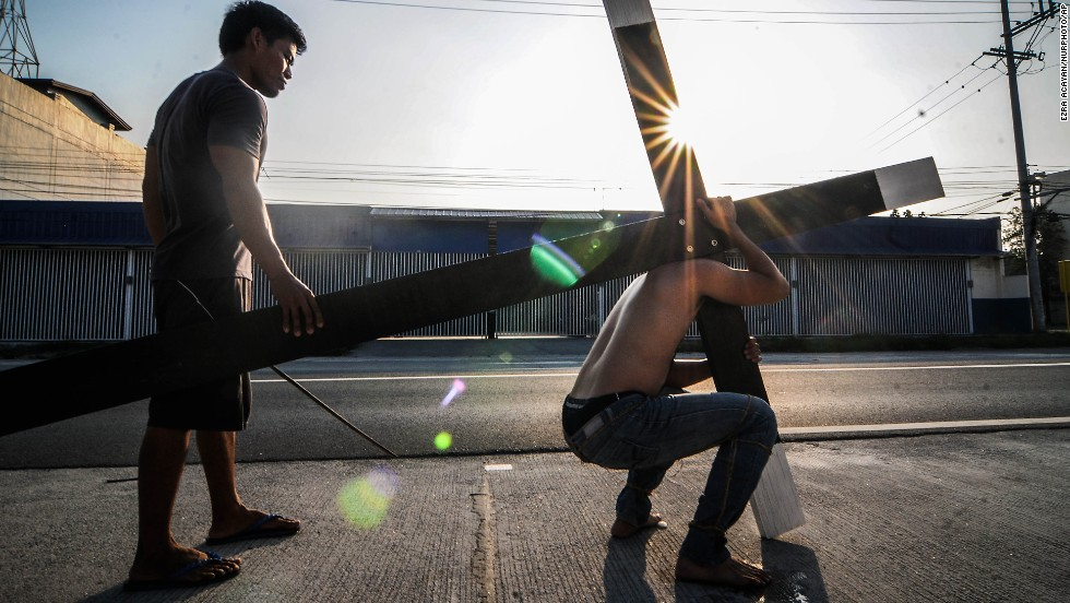 A Filipino carries a wooden cross along a road on Maundy Thursday in San Fernando, Pampanga province, Philippines, on April 17.