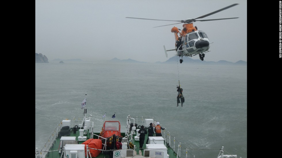 "A member of the South Korean Coast Guard is pulled up from a helicopter while working at the site of a capsized ferry Wednesday, April 16, near Jindo, South Korea. The ferry was carrying hundreds of people, many of them high school students on a field trip, when <a href=""http://www.cnn.com/2014/04/15/asia/gallery/south-korea-sinking-ship/index.html"">it started sinking</a> on Wednesday morning. At least 25 people were confirmed dead as of Thursday, April 17, and while nearly 200 passengers had been rescued, nearly 300 remained unaccounted for."