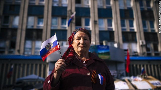 An elderly woman holds a Russian flag outside the secret service building in the eastern Ukrainian city of Lugansk on April 16, 2014.