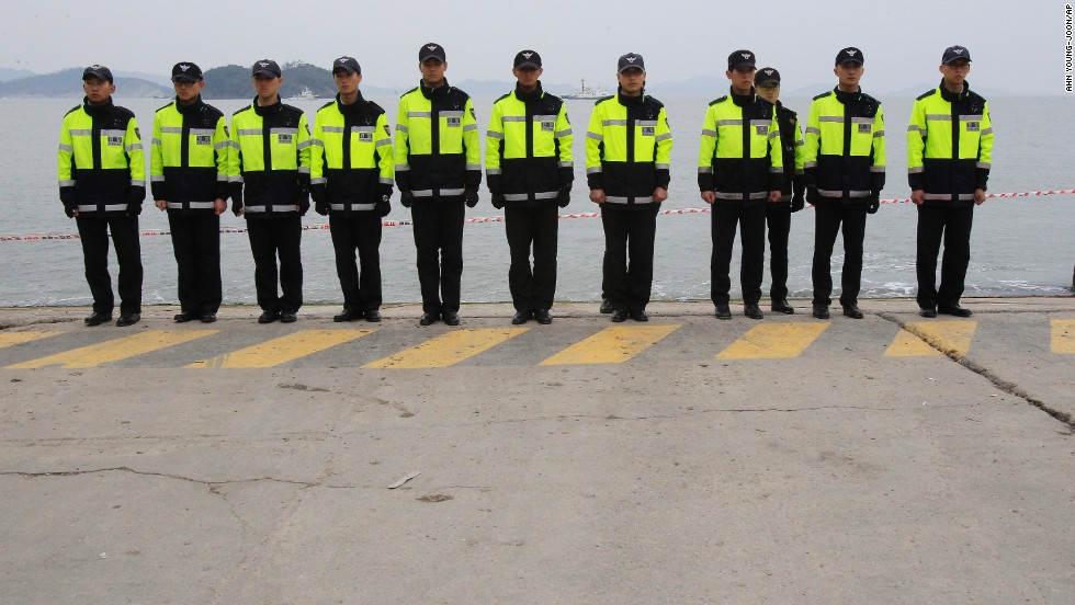 Police officers in Jindo stand guard Saturday, April 19, to prevent relatives of the ferry's missing passengers from jumping in the water. Some relatives said they will swim to the shipwreck site and find their missing family members by themselves.