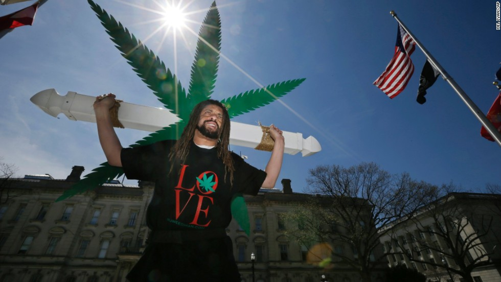 Ed Forchion, a pro-marijuana activist known as NJ Weedman, carries a large cross with huge likeness of a marijuana leaf on April 20 as he walks in front of the New Jersey Statehouse in Trenton, New Jersey. Dozens of activists and community members gathered in front of Statehouse to show their support for legalizing marijuana.