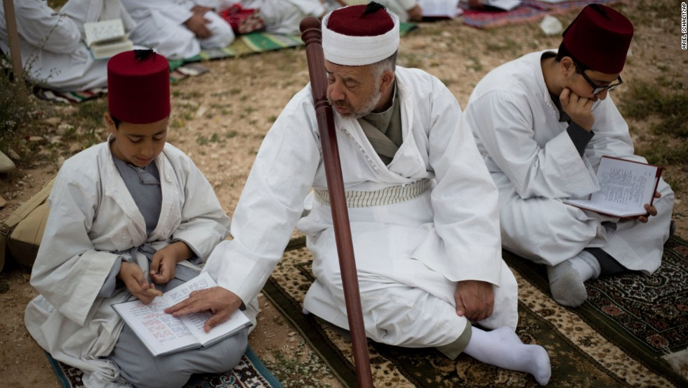 Members of the ancient Samaritan community read from a holy book during the pilgrimage for the holy day of Passover at the top of Mount Gerizim near the West Bank town of Nablus, early Sunday, April 20.  Passover began on April 14 this year and ends on April 22.