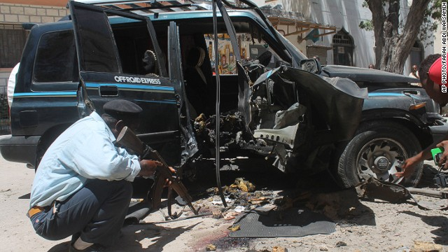 A Somali police officer looks at the wreckage of the car in Mogadishu, Somalia, on Monday.