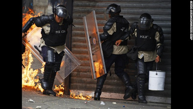 A police officer runs away from a fire set off by a Molotov cocktail thrown by protesters in Caracas on April 17.
