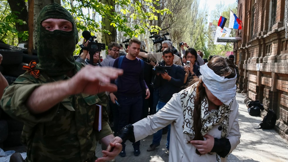 "A pro-Russian armed man escorts Ukrainian journalist Irma Krat after news conference in Sloviansk, Ukraine, on Monday, April 21. Ukraine has seen a sharp <a href=""http://www.cnn.com/2014/03/26/world/gallery/ukraine-crisis/index.html"">rise in tensions</a> since a new pro-European government took charge of the country in February."