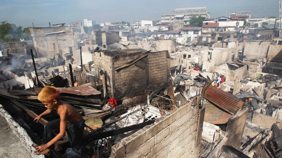 A boy climbs out of a charred shanty as he collects reusable materials after a fire razed a slum in Caloocan, Philippines, on Monday, April 21.