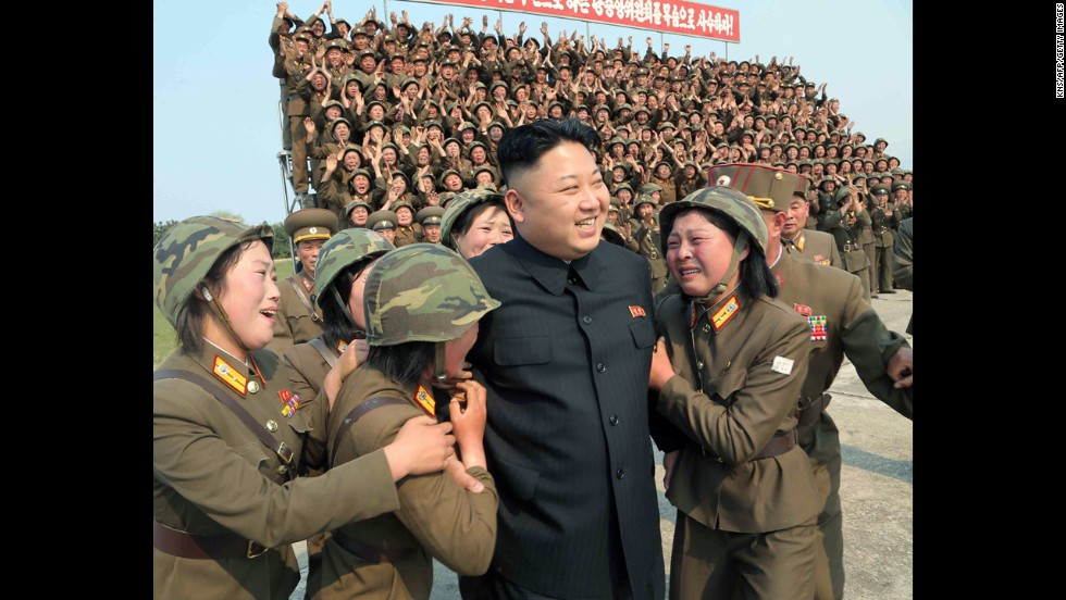 North Korean leader Kim Jong Un smiles with female soldiers after inspecting a multiple-rocket launching drill at an undisclosed location. The undated photo was released on Thursday, April 24, by North Korea's official Korean Central News Agency.