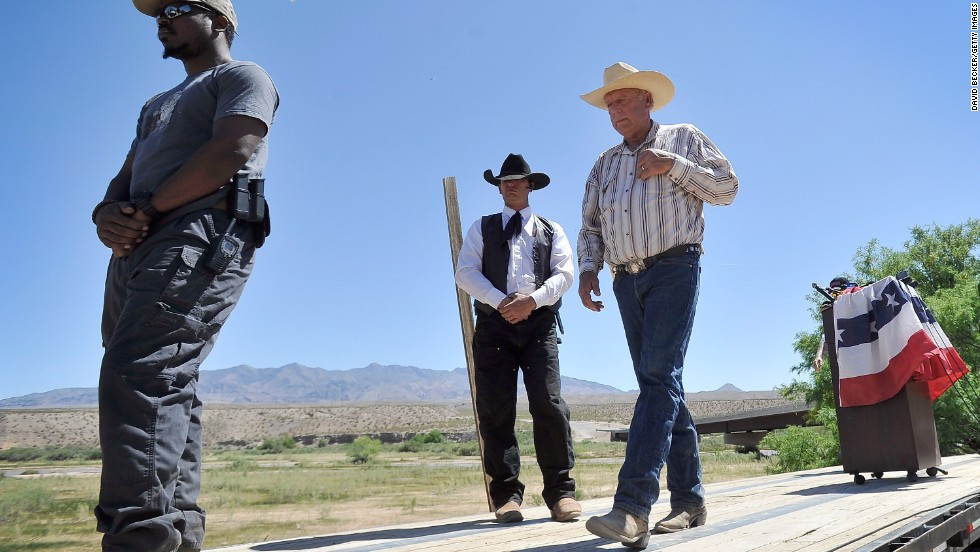 Rancher Cliven Bundy, right, leaves the podium with bodyguards after a news conference near his ranch in Bunkerville, Nevada, on Thursday, April 24.  Bundy and the Bureau of Land Management have been locked in a dispute for a couple of decades over grazing rights on public lands.