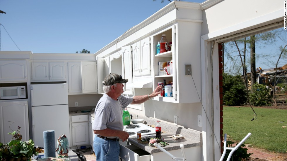 Jerry Estes salvages food items April 30 from the kitchen of his home that was damaged by a tornado in Louisville.