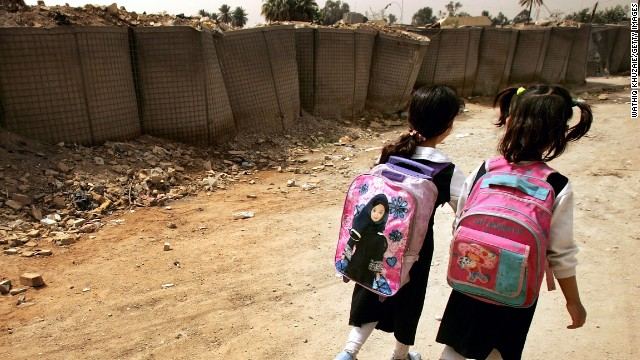 Internally displaced girls go to school on March 19, 2008 as they live in a bombed building in Baghdad, Iraq.