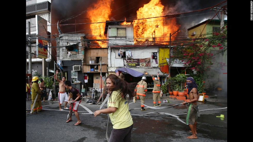 Residents help firefighters put out a blaze that engulfed a poor neighborhood in Manila, Philippines, on Tuesday, April 29.