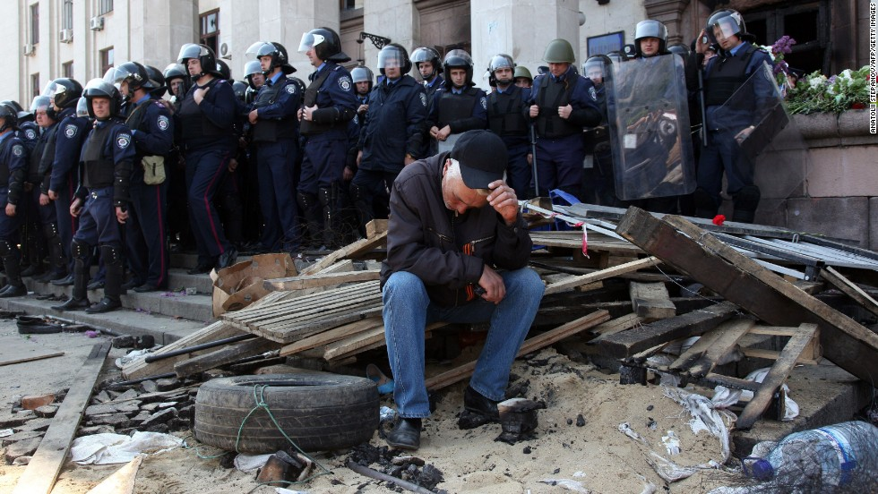 A pro-Russian activist sits in front of policemen guarding the burned trade union building in Odessa on May 3.