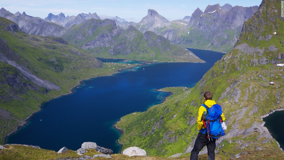 "A hiker enjoys a sunny day on the Lofoten islands in <strong>Norway</strong>, the second happiest country.  According to the research, Norway ranks above average in all of the 11 dimensions that the OECD considers as ""essential to a good life."""