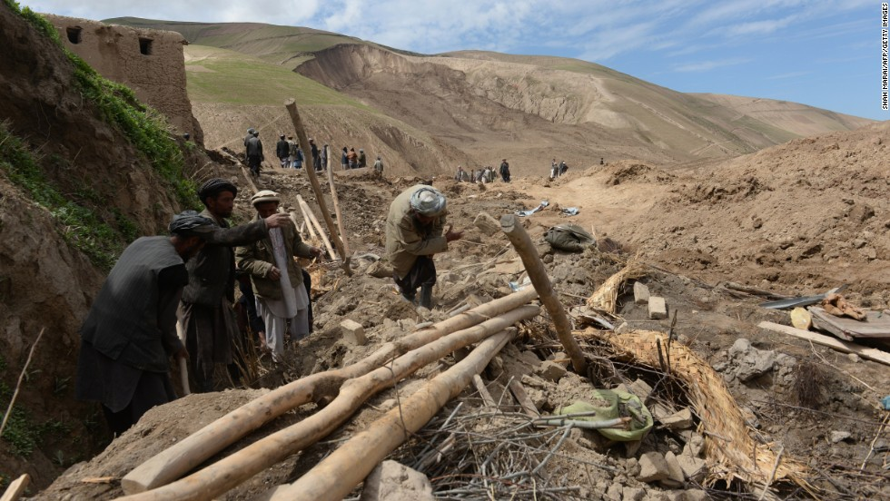 Villagers search through debris on May 5.