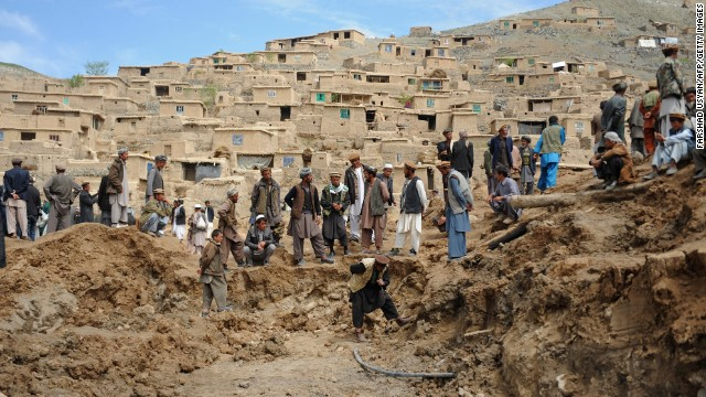 Afghan villagers search through dirt at the scene in the landslide-hit Aab Bareek village in Argo district of Badakhshan on May 5, 2014.