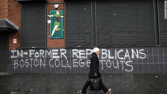 "A woman passes graffiti on the Falls Road referring to former Republicans who took park in the Boston college tape recordings in West Belfast, Northern Ireland on May 4, 2014. Tensions in Northern Ireland rose on May 3 after police obtained an extension to question detained republican leader Gerry Adams over a notorious IRA murder. In 2001, Boston College, a prestigious Catholic institution, researchers embarked on a project to interview participants in the Northern Ireland conflict known as the Troubles. They set about constructing an oral history of the violent period, interviewing dozens of former Irish Republican Army members and participants in voluntary paramilitary groups that supported union with Britain. Interviewees were promised absolute anonymity until after their deaths. That guarantee unraveled amid court orders, with potentially serious consequences for participants in Ireland, and fresh questions about academic freedom and the strength of researchers' confidentiality assertions in the face of a criminal investigation. ""Boston College sold us out, "" Belfast Project founder and journalist Ed Moloney told AFP, saying the school capitulated almost immediately when court officials demanded the recordings. . AFP PHOTO / PETER MUHLYPETER MUHLY/AFP/Getty Images"