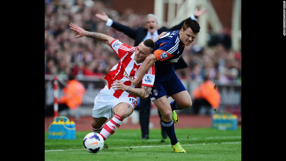 Marko Arnautovic of Stoke City, left, and John Arne Riise of Fulham challenge for the ball Saturday, May 3, as Stoke City manager Mark Hughes appeals in the background. Stoke City won the match 4-1, and the result meant that Fulham would be relegated from the English Premier League after a 13-year stay.