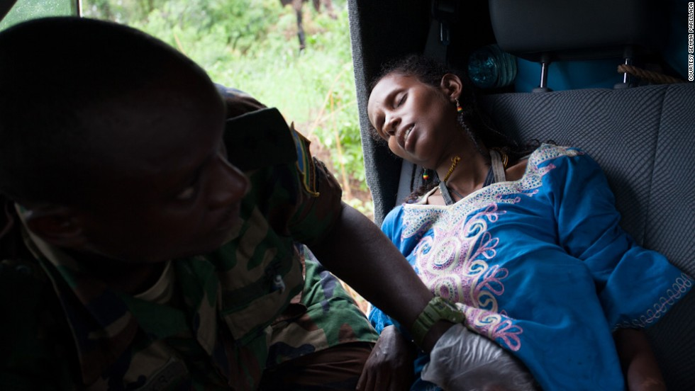 A man tends to a woman in labor along the road near Sibut, Central African Republic. She was one of three women who gave birth to five babies during the journey.