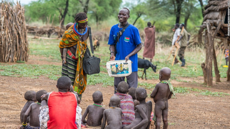 In South Sudan, area supervisor Paulo Lovul and village volunteer Aleper Akol Naparinga use visual aids such as picture books to teach people how to avoid contracting Guinea worm.