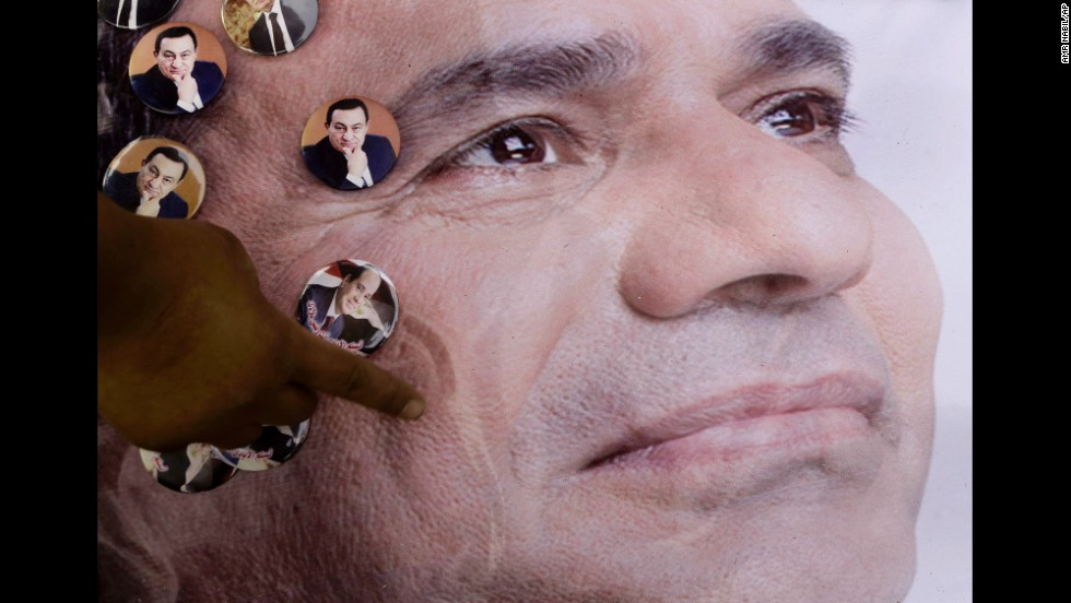 A man pins pictures of former Egyptian President Hosni Mubarak on a poster showing presidential hopeful Abdel Fattah el-Sisi on Sunday, May 4, in Cairo. El-Sisi and Hamdeen Sabahi are vying for the country's top post, with the first round of voting scheduled for May 26-27.