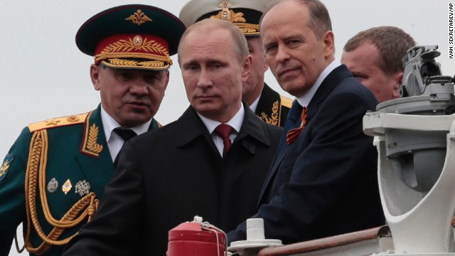 Russian President Vladimir Putin, flanked by Defense Minister Sergei Shoigu, left, and Federal Security Service Chief Alexander Bortnikov, right, arrives a Victory Day celebration after inspecting battleships in Sevastopol, Crimea.