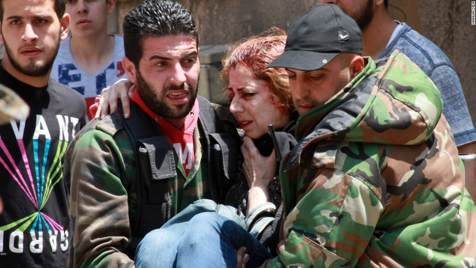 A woman injured when a mine went off is carried in Homs on May 10.